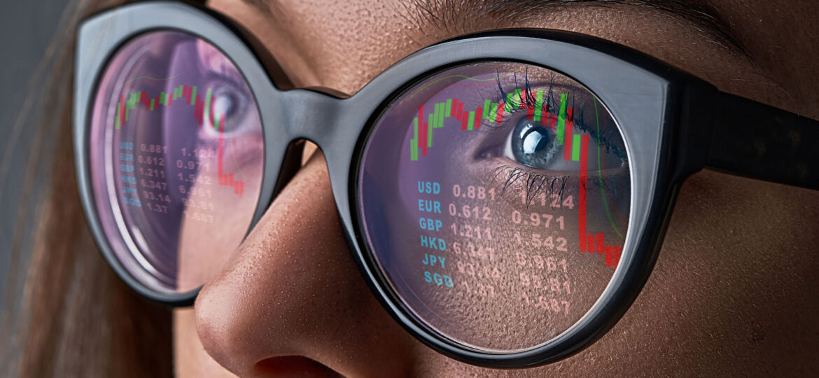 Business woman with glasses looks at stock market quotes and exc